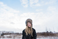 Portrait of confident girl wearing warm clothing while standing against cloudy sky during winter - CAVF57312