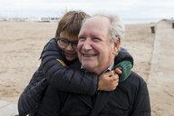 Playful grandson piggybacking on cheerful grandfather at beach - CAVF57318