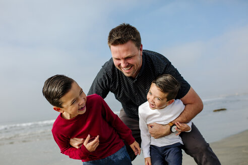 Cheerful father playing with sons at beach - CAVF57324