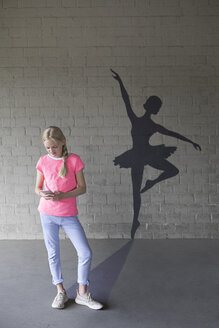 Blond girl with smartphone and shadow of ballerina in the background - PSTF00266