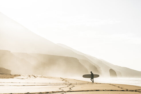 Man with surfboard standing on shore at beach against clear sky during foggy weather - CAVF57364