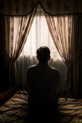 Rear view of senior man sitting on bed against curtains hanging window in darkroom - CAVF57391