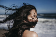 Close-up of teenage girl with tousled hair at beach - CAVF57394