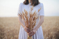 Midsection of woman holding wheat crops while standing against sky at farm - CAVF57403