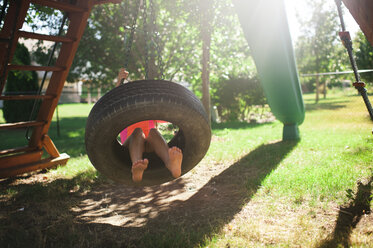 Low section of boy swinging in tire swing at playground - CAVF57418