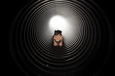 Portrait of playful boy lying in huge metallic pipe - CAVF57421