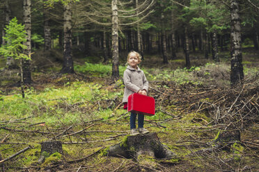 Full length of girl with red briefcase standing on tree stump at forest - CAVF57442