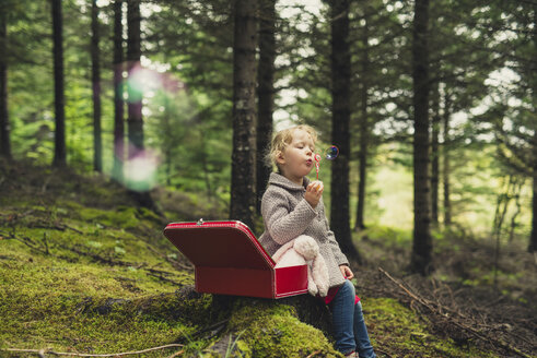 Girl blowing bubbles while sitting at forest - CAVF57445