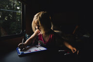 Girl drawing on slate while sitting in darkroom at home - CAVF57451