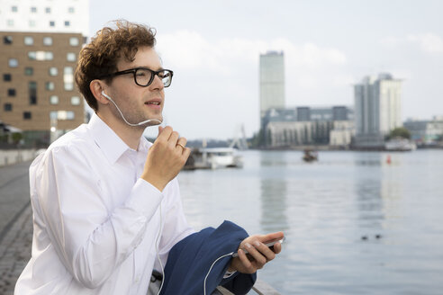 Germany, Berlin, businessman using smartphone and earphones outdoors - FKF03104