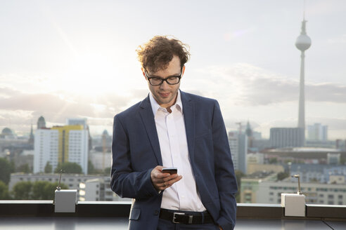 Germany, Berlin, businessman on roof terrace looking at smartphone in the evening - FKF03119