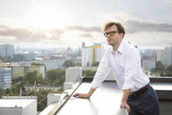 Germany, Berlin, portrait of businessman on roof terrace looking at view - FKF03125