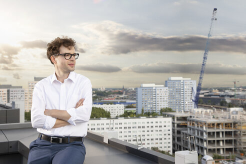 Germany, Berlin, content businessman on roof terrace looking at view - FKF03128