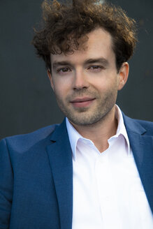 Portrait of smiling businessman with stubble and curly brown hair - FKF03131