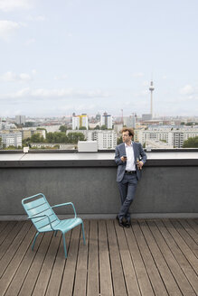 Germany, Berlin, businessman relaxing on roof terrace with a drink - FKF03134