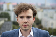 Portrait of businessman with stubble and curly brown hair on roof terrace in the evening - FKF03137