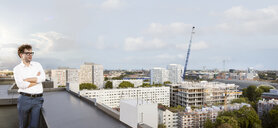Germany, Berlin, businessman standing on roof terrace looking at view - FKF03140