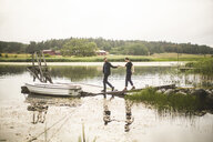 Couple holding hands while walking towards jetty over lake during weekend getaway - MASF09709