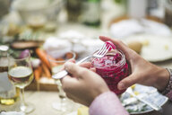 Cropped image of man removing pickle from jar at table during dinner party - MASF09712