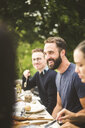 Smiling man looking away while enjoying dinner party with friends in backyard - MASF09715