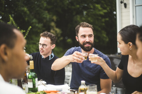 Man and woman toasting drinks while enjoying dinner party with friends in backyard - MASF09718