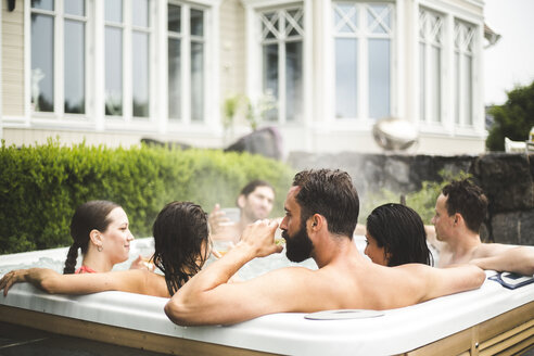 Mid adult man drinking alcohol while enjoying with friends in hot tub during weekend - MASF09727