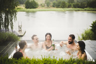 Cheerful male and female friends enjoying drinks in hot tub against lake during weekend getaway - MASF09730