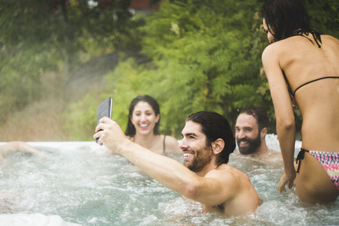 Young man taking selfie through mobile phone while friends enjoying in hot tub during weekend getaway - MASF09733