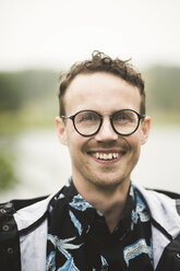 Portrait of smiling mid adult man wearing eyeglasses during dinner party in backyard - MASF09739