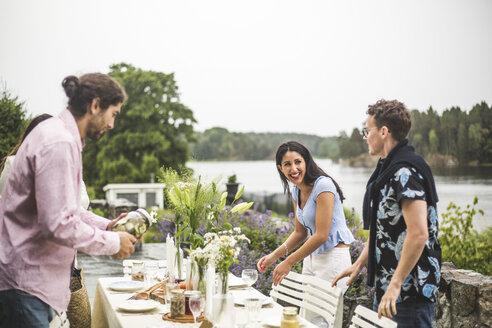 Happy multi-ethnic friends setting table for dinner party in backyard against clear sky - MASF09745