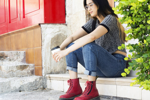 Fashionable young woman wearing  red boots sitting with coffee to go on steps - LMJF00007