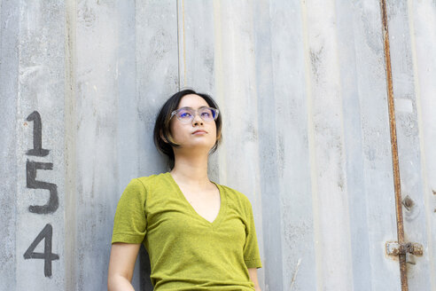 Portrait of young woman wearing  glasses leaning against wall - LMJF00010
