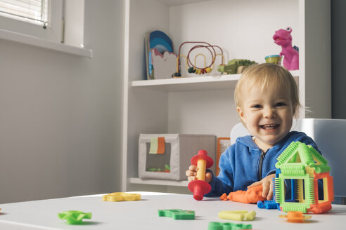 Portrait of laughing baby girl playing with modeling clay in children's room - MOMF00550