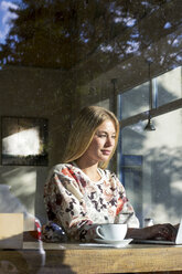 Portrait of blond woman working on laptop in a cafe - LMJF00019