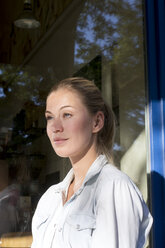Portrait of smiling woman in front of window looking at distance - LMJF00025