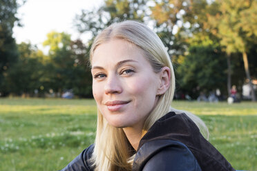 Portrait of content blond woman relaxing in a park - LMJF00031