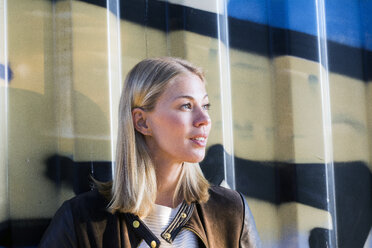 Portrait of blond woman in front of container looking at distance - LMJF00034