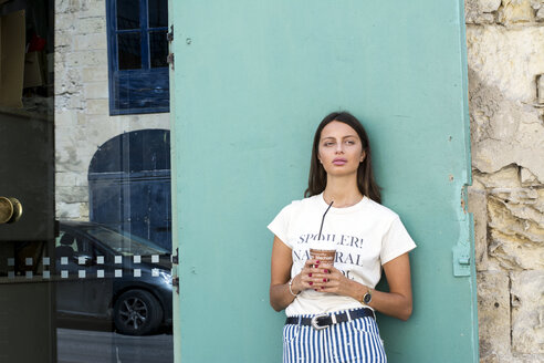 Portrait of young woman with paper cup of iced coffee - LMJF00037