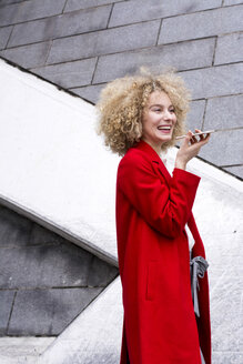 Portrait of laughing blond woman with ringlets wearing red coat talking on mobile phone - LMJF00049