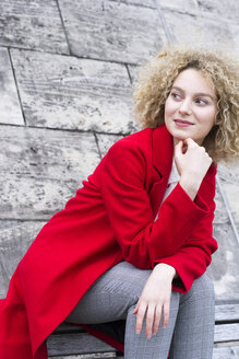 Portrait of smiling blond woman with ringlets wearing red coat watching something - LMJF00052