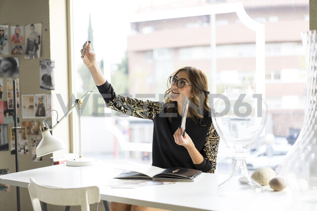 Smiling young designer taking selfie with smartphone in an atelier - AFVF02047