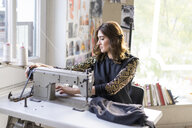Young designer using sewing machine in an atelier - AFVF02056