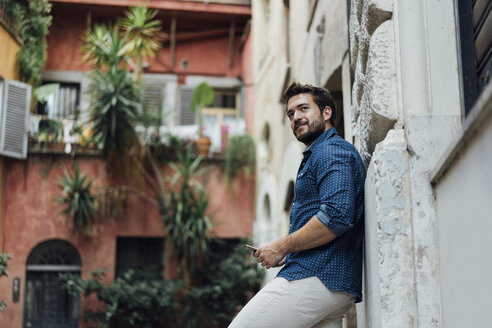 Bearded man with smartphone leaning against facade looking at distance - BOYF01077
