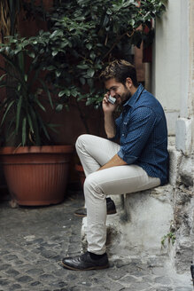 Smiling businessman on the phone sitting on steps in a courtyard - BOYF01080