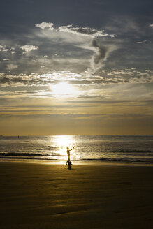Netherlands, Cadzand-Bad, silhouette of person taking selfie on the beach at twilight - SKA00064