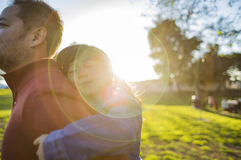 Cute little girl napping while father piggybacking her in park on sunny day - TGBF01745