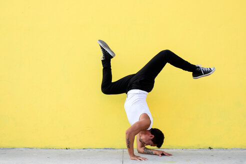 A man balancing a yoga pose against a yellow wall - INGF08095
