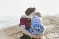 Affectionate mother holding daughter on sunny beach - CAIF22255