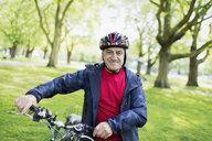 Portrait confident active senior man riding bike in park - CAIF22261