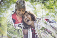 Happy active senior women friends hugging after sports race, wrapped in thermal blanket - CAIF22282